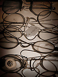 Old fashioned eye glasses and a glass eye in sepia.