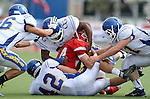 SIOUX FALLS, SD - SEPTEMBER 7:  Connor Burchill #14 from Lincoln is brought down by a host of Knights including Isaac Althoff #42 from O'Gorman in the first quarter of their game at the 2013 Presidents Bowl at Howard Wood Field. (Photo by Dave Eggen/Inertia)