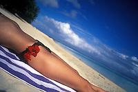 Woman sunbathing on the beach with a hibiscus flower in her bikini.