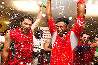 Richard Castillo (12) and Audry Perez (5) of the Springfield Cardinals, right, celebrate in the clubhouse after beating the Tulsa Drillers in the North Division Championship game at Hammons Field on September 9, 2012 in Springfield, Missouri. (David Welker/Four Seam Images)