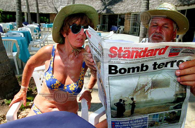 The day after the terrorist attacks in Mombasa, tourists read newspaper reports on the terrace of a nearby holiday resort..13 people were killed when a car bomb exploded outside the Israeli-owned Paradise Hotel, at the same time as a failed rocket attack on an Israeli airliner taking off from Mombasa. A statement from al Qaeda claimed responsibility.