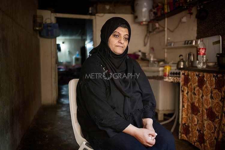 29/08/15. Shaqlawa, Iraq. -- Sabah, 48 y.o. from Falluja inside her house, in the basement of a residential complex. Sabah left Falluja when the bakery of her son Omar was hit by a barrel bomb which killed him. She lives with her 4 children and pay 350.000 IQD for rent each month. He husband lives in Baharka camp, Erbil with his new wife, and only comes to Shaqlawa to freshen up when Erbil gets too hot. <br /> <br /> &quot;I could not sleep last night: I was thinking of the rent, and how to pay it. I sold all we had just to pay rent, but now we have nothing left&quot;.