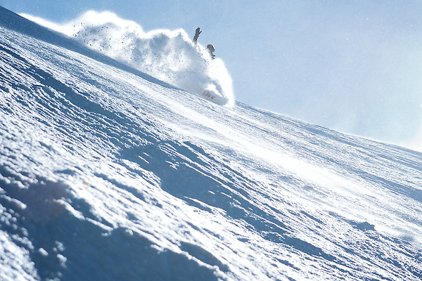 Snowboarder landing in fresh powder.