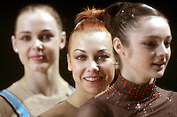 (Center) Natalya Godunko of Ukraine (in focus) smiles to camera during All-Around awards ceremony at 2006 Thiais Grand Prix in Paris, France on March 25, 2006. Background left and right are teammates Galina Shirkina and Anna Bessonova of Ukraine.  (Photo by Tom Theobald)
