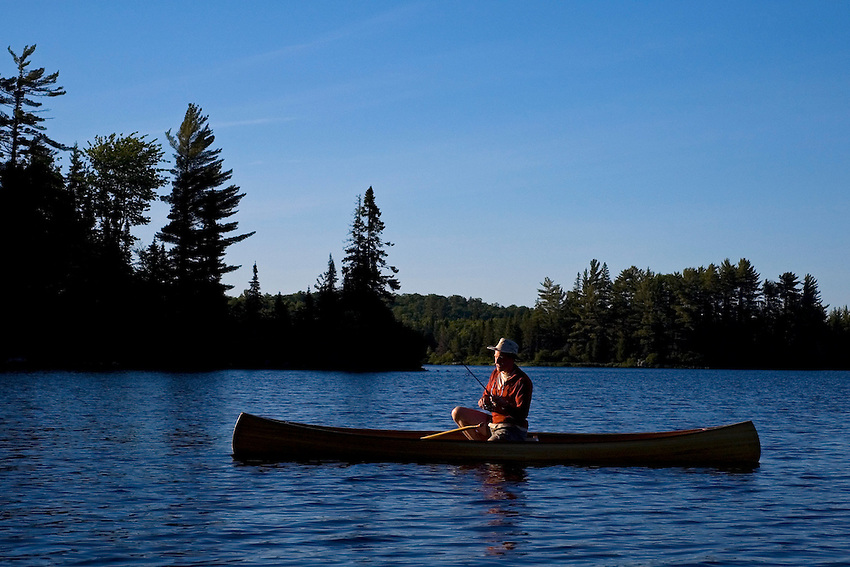 A man fishes from a cedar strip solo canoe in Craig Lake State Park near Michigamme Michigan.