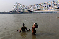 Men bathe in the Ganges River in central Kolkata beside the Howrah bridge.<br />