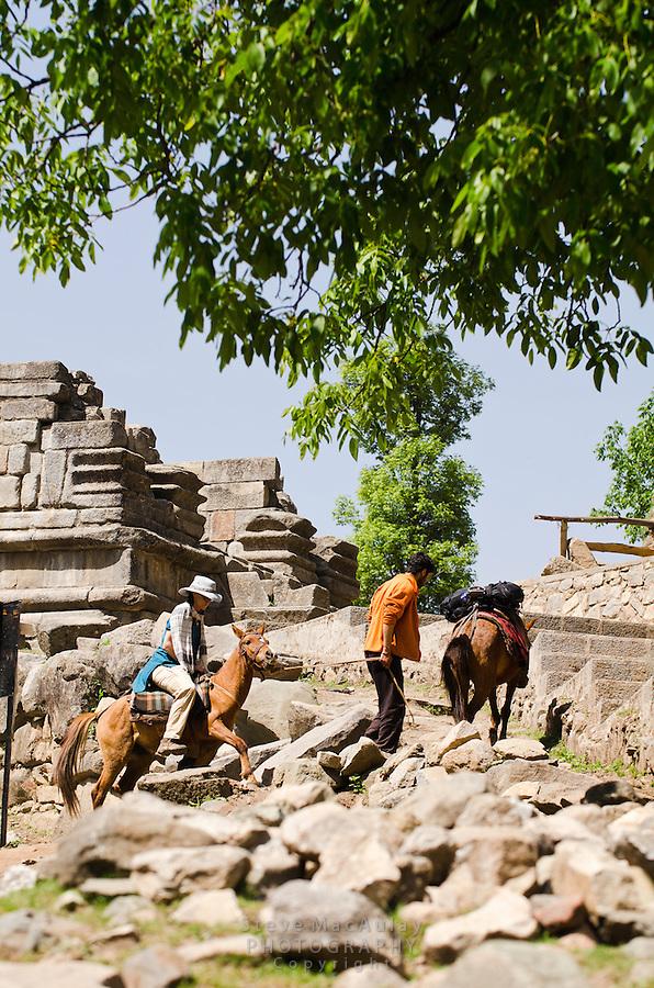 Western tourist riding small horse through the ruins at Naranag, Kashmir, India.