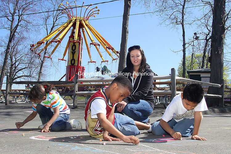 "MIDDLEBURYCT.-09 APRIL 2010-041510DA01-Art Teacher of Driggs Elementary School in Waterbury Andrea LaFrance watches over her students from left, Amber Ortiz, 9, Verigo Bonaparte, 10, and Carlos Barvera, 8, as they take part in sidewalk art with patriotic theme during a special ""The Spring Break Experience"" at Quassy Amusement Park (camp Quassy for this week.) funded by a special grant through State of Connecticut. The 5-day program ran from Monday-Friday 9-2 and was open to 400 selected student grades 4-7 from Waterbury Public Schools. Goal of project is to provide academic enrichment and recreational experiences for literacy, numeracy, science, technology, health/athletics and a reward day to enjoy the rides in the park. A curriculum was created in collaboration with the school site academic teams, the recreation leaders for the City and the educational program coordinators at Quassy Amusement Park.  Darlene Douty Republican-American"