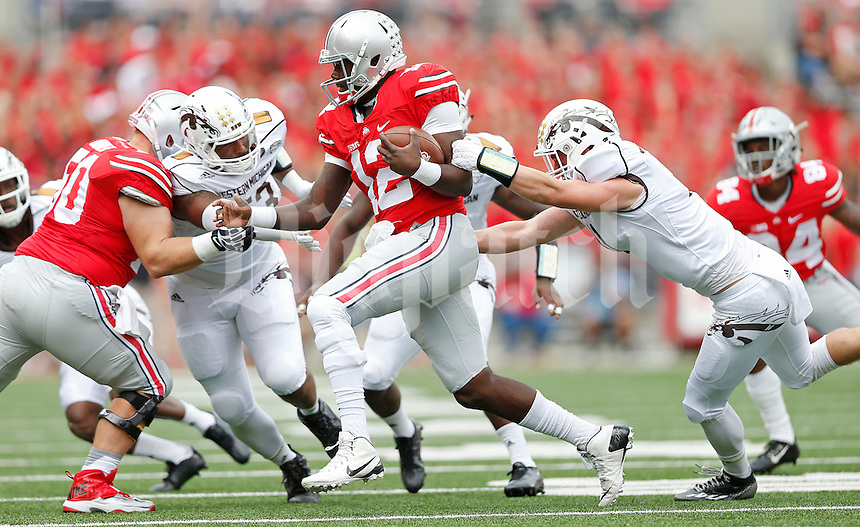 Ohio State Buckeyes quarterback Cardale Jones (12) breaks a tackle from Western Michigan Broncos linebacker Austin Lewis (11) in the first quarter of the college football game between the Ohio State Buckeyes and the Western Michigan Broncos at Ohio Stadium in Columbus, Saturday afternoon, September 26, 2015. At half time the Ohio State Buckeyes led Western Michigan Broncos 24 - 6. (The Columbus Dispatch / Eamon Queeney)