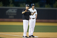 Wake Forest Demon Deacons head coach Tom Walter (16) gives instructions to DJ Poteet (4) during the game against the North Carolina State Wolfpack at David F. Couch Ballpark on April 18, 2019 in  Winston-Salem, North Carolina. The Demon Deacons defeated the Wolfpack 7-3. (Brian Westerholt/Four Seam Images)