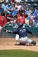 Charleston RiverDogs catcher Charleston RiverDogs Eduardo Navas (20) shows the umpire the ball as Jose Almonte (9) of the Hickory Crawdads slides safely across home plate at L.P. Frans Stadium on May 13, 2019 in Hickory, North Carolina. The Crawdads defeated the RiverDogs 7-5. (Brian Westerholt/Four Seam Images)