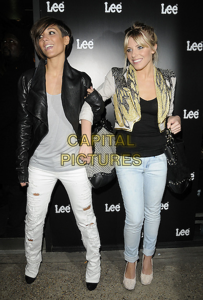 FRANKIE SANDFORD & MOLLIE KING of The Saturdays.Lee Jeans store relaunch party at Lee store, Carnaby Street London England.31st March 2010.full length jeans denim black top white ripped torn leather black gold shoulder pads arms linked bag purse.CAP/CAN.©Can Nguyen/Capital Pictures.