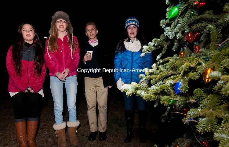 TORRINGTON, CT-120414JS08- Students from the Warner Theatre Center for the Arts and Education, from left, Hannah Begley, 14, of Avon; Julia Traub, 16, of Torrington ; Jacob Honig, 15, of Torrington and Catherine MacKay, 16, of Farmington, sing carols during the annual North End Community Association's Christmas Tree lighting ceremony Thursday at the Torrington Police Station. The Torrington Police Department will hold its annual Tip-A-Cop fund raiser tonight (Friday) from 5-8 pm.m at the 99 Restaurant in Torrington to benefit the Special Olympics. <br /> Jim Shannon Republican-American