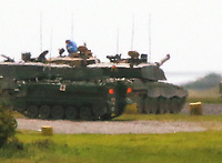 Thursday 15 June 2017<br /> Pictured: Two men in forensics suits on top of a tank, believed to be the one involved in the fatal incident in Castlemartin range.<br /> Re: A soldier has been killed and three others injured after an incident involving a tank at a Ministry of Defence base in Pembrokeshire.<br /> The soldier, from the Royal Tank Regiment, died in the incident at Castlemartin Range.<br /> Two people were taken to Morriston Hospital in Swansea, while another casualty remains in Cardiff's University Hospital of Wales.<br /> An investigation is under way.<br /> Live firing was scheduled to take place at the range between Monday and Friday.<br /> In May 2012, Ranger Michael Maguire died during a live firing exercise at the training base. An inquest later found he was unlawfully killed.