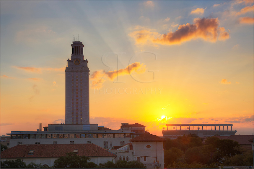 Looking east, this photo from Austin, Texas, shows the University of Texas Tower at sunrise. The sun was just breaking over the clouds, creating  contrasting light trails streaming to the sky. In the distance rising from the 40-acres campus is the iconic UT Tower. To the right is DKR Texas Memorial Stadium.