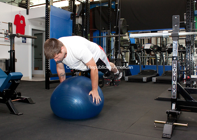 WATERBURY, CT- JUNE 20 2011-062012DA04- Troy Michaud, a Trainer at Poundstone Performance Training Center demonstrates a push up on a stability ball during a training session inside their new facility located on Baldwin Street in Waterbury on Wednesday..Darlene Douty Republican American