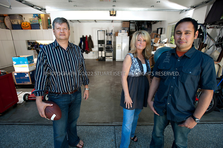 7/8/2010--Sammamish, WA, USA...Steve Stone (left), the founder and chief executive of InfoFlows. Also, two co-founders, Megan Kahn (center) and Carlo Martin (right). The company started in Stone's garage, seen here with the company's servers in the back, and it's been forced to return there since a legal dispute with Corbis put it in mothballs...Corbis, Bill Gates's photo archive and digital image distribution business, had a deal with InfoFlows, which created image tracking technology useful in Corbis's business. But the relationship turned sour, and InfoFlows, whose founder and chief executive, Mr. Stone, is a former Microsoft manager, sued Corbis, charging theft of intellectual property and fraud. Corbis lost the case, and has been fined $20 million...©2010 Stuart Isett. All rights reserved.