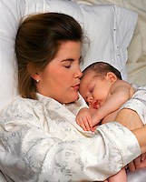 New mother lying in bed and holding her sleeping newborn infant.