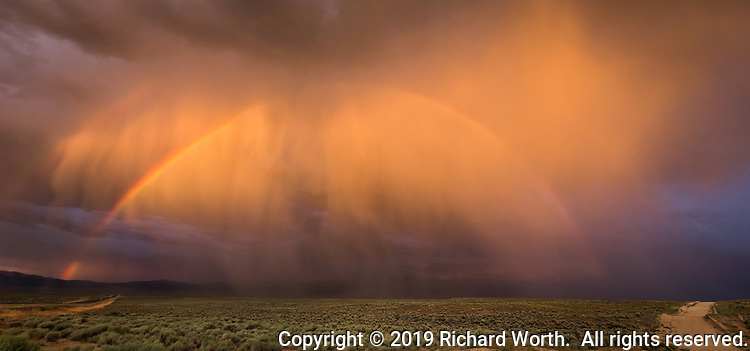 A rainbow, with hints of a second rainbow above it, at sunset along U.S. Highway 50 west of Austin, Nevada.