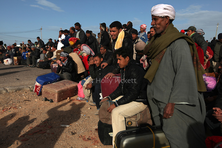 A crowd of men wait for a bus at the Tunisia-Libya border near Ben Guerdane, Tunisia, Friday, Feb. 26, 2011. Thousands of foreign workers continued their exodus across the border into Tunisia, fleeing violence sparked by an uprising against Col Muammar Qaddafi. The refugees, primarily Egyptians, had to wait at the border or at an improvised camp nearby until a bus could take them to the airport in Tunis, but the number of people waiting far exceeded the seats available on the buses.