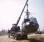 A crashed UH-1 Huey helicopter is hoisted by a crane truck. This images is from the collection of J.W. Womble of the 610th Transportation Company during the Vietnam War.
