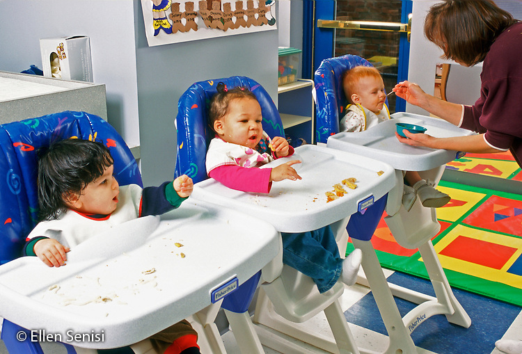 MR/ Schenectady, New York.Schenectady Day Nursery: private non-profit daycare.Infant class / Babies eat lunch, aide helps. Left to right: boy: 12 months (Puerto-Rican-American) / girl: 12 months (African-American-Caucasian) / girl:7 months (Native-American-Caucasian).MR:Vro1, Kin7, Bru2, Ada4      FC#:21805-00319.scan from slide.© Ellen B. Senisi