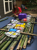 """READING INSPIRED RAFT<br />Clayton Niederman, 10, works on a raft Clayton and his brother, Edmond Niederman, 12, made from bamboo and empty plastic jugs that became the raft's floatation. The boys got the idea to build the raft after reading a book, """"The Raft"""" about a boy in Maine who paddled a raft, said their mom, Gina Niederman of Fayetteville. Brisk sales of kayaks made it difficult for the family to find kayaks to buy and that sparked the project.<br />(Courtesy photo)"""