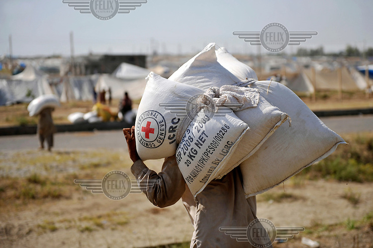 Refugees from Swat district carry goods received from the Red Cross/Red Crescent (ICRC) to their tents at the Swabi Refugee camp. The camp is run by Red Cross/Red Crescent (ICRC), and currently houses around 18,000 refugees. The Pakistani government began an offensive against the Taliban in the Swat Valley in April 2009, which led to a major humanitarian crisis. Up to two million civilians were estimated to have been displaced by the fighting.