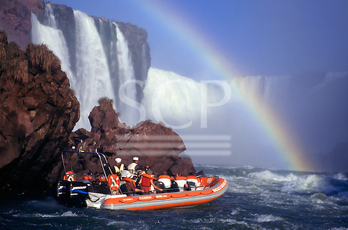 Iguassu Falls, Parana State, Brazil. Tourists on the boat at the foot of the waterfalls; rainbow.