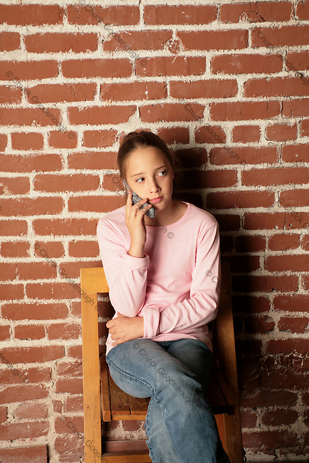 Photo of a Preteen Girl Sitting on a Folding Chair while Talking to her Mother on her Mobile Phone.