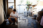 Xavier Ruiz writes song lyrics at his home next to grey water from his laundry in the Rancho Garcia trailer park in Thermal, Calif., March 9, 2012.