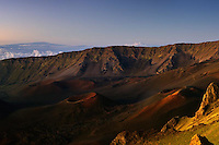 Golden glow of sunrise enhances the beauty of the Haleakala Crater on Maui in Hawaii with the Big Island in the background