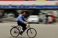 A man cycles along a Shenzhen street, China..28 Apr 2006