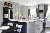 An informal dining area with a dark blue banqutte sits next to the kitchen island which also acts as a breakfast bar and additional work surface