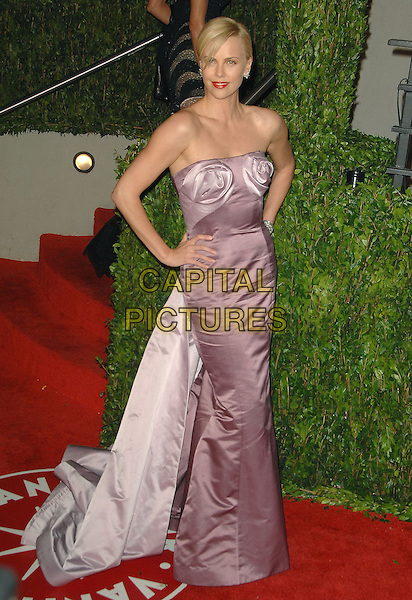 CHARLIZE THERON.The 2010 Vanity Fair Oscar Party held at The Sunset Tower Hotel in West Hollywood, California, USA..March 7th, 2010.oscars full length pink two tone bustier bodice maxi gown couture fishtail silk satin strapless hand on hip .CAP/RKE/DVS.©DVS/RockinExposures/Capital Pictures.