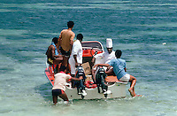 A chef in his full uniform supervises the transportation of food to an island restaurant off the east coast of Mahe.