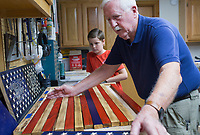 NWA Democrat-Gazette/CHARLIE KAIJO Don Lowe (right) and his grandson Jeremiah Lowe, 11, (back) create an American flag out of wood pieces, Monday, August 12, 2019 at Don's home in Bella Vista.<br /> <br /> Don Lowe and his grandson, Jeremiah Lowe, 11, turned their woodcrafting hobby into a business nine months ago after Don sold one of his wooden flags on Facebook within the first hour of posting it. It's a casual hobby he and his grandson share but they've sold 30 now in over four states, many to retired and active service members and emergency responders. He is working on a wooden flag he and his grandson will donate to the Bella Vista Fire Department.