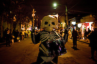 A drummer in the Skeleton Krewe leads Le Krewe d'Etat down Magazine Street at Mardi Gras in New Orleans, Louisiana, USA.