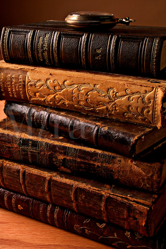 Stack of old antique books with pocket watch