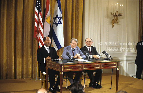 United States President Jimmy Carter, center, makes remarks as President Anwar Sadat of Egypt, left, and Prime Minister Menahem Begin of Israel, right, look on prior to signing the Camp David Accords at a ceremony in the East Room of the White House in Washington, D.C. on September 17, 1978..Credit: Arnie Sachs / CNP
