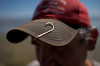 Commercial fisherman Brian Jourdain keeps a fish hook on the brim of his cap for good luck, at Clear Lake, in Lakeport, Calif., on July 12, 2013. (Alvin Jornada / For The Press Democrat)
