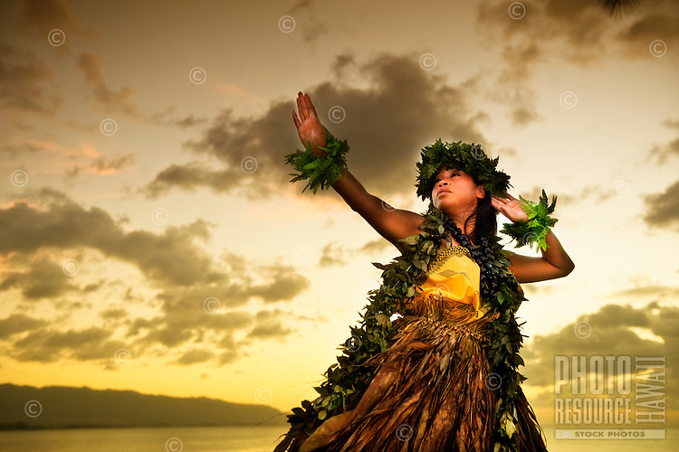 Hula kahiko dancer by the ocean at sunset, O'ahu.