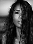 Sensual black and white beauty portrait of a young woman exotic mixed-race ethnicity face with long dark hair and sand particles on her hair and skin Image © MaximImages, License at https://www.maximimages.com