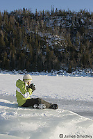 Young girl drinking hot chocolate outside on the frozen lake ice