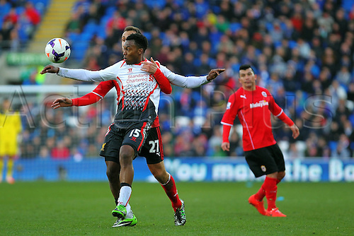 22.03.2014  Cardiff, Wales. Daniel Sturridge of Liverpool is held up by Torres Ruiz  during the Premier League game between Cardiff City and Liverpool from Cardiff City Stadium.