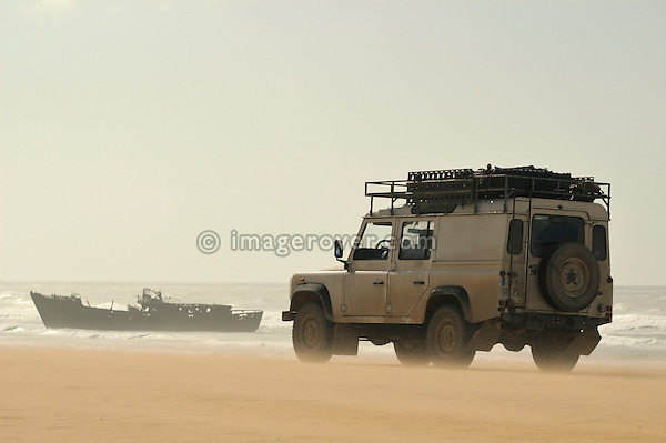 Africa, Morocco, Western Sahara, between Laayoune and Dakhla. Land Rover Defender on a beach against a ship wreck. --- Releases available! Automotive trademarks are the property of the trademark holder, authorization may be needed for some uses.