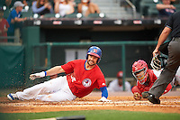 Buffalo Bisons first baseman Casey Kotchman (55) slides into home as catcher Raffy Lopez (9) applies the tag during a game against the Louisville Bats on June 20, 2016 at Coca-Cola Field in Buffalo, New York.  Louisville defeated Buffalo 4-1.  (Mike Janes/Four Seam Images)