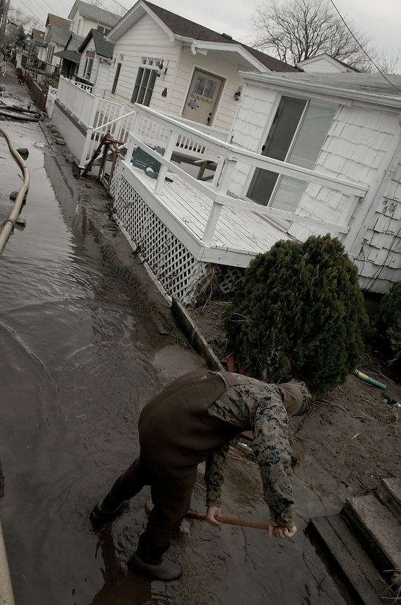 Member of the US army helps the residents of Breezy Point, NY. The village was devastated by Hurricane Sandy. More than 80 homes were destroyed and 110 burned to the ground this night.