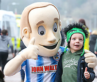 A young Huddersfield Town fan has his photo taken with a mascot<br /> <br /> Photographer Alex Dodd/CameraSport<br /> <br /> The Premier League - Huddersfield Town v Swansea City - Saturday 10th March 2018 - John Smith's Stadium - Huddersfield<br /> <br /> World Copyright &copy; 2018 CameraSport. All rights reserved. 43 Linden Ave. Countesthorpe. Leicester. England. LE8 5PG - Tel: +44 (0) 116 277 4147 - admin@camerasport.com - www.camerasport.com