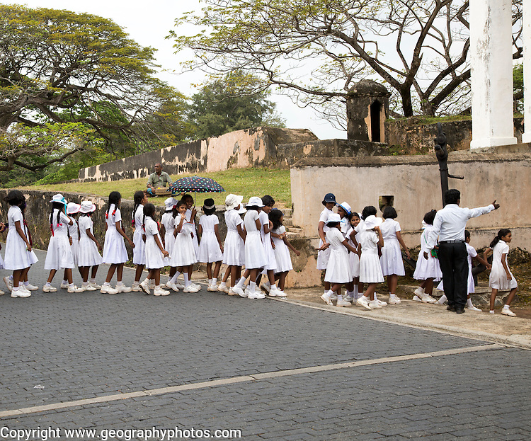 School children in uniform walking in a street in the historic town of Galle, Sri Lanka, Asia